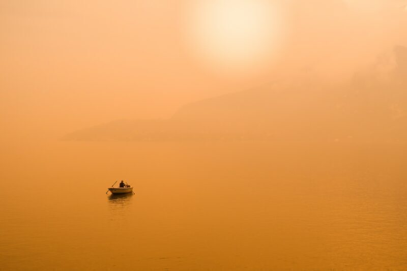 Man sitting in a boat in the middle of a lake