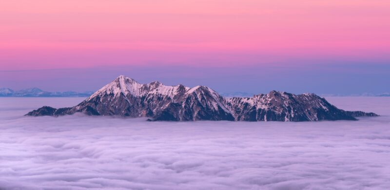 Grey rock mountains rising above clouds