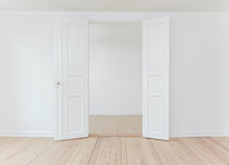 White color open door and wall with a wooden floor